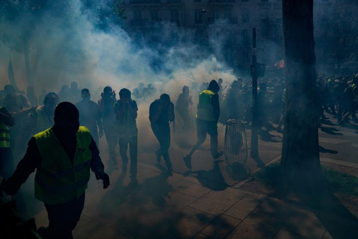 """Des """"gilets jaunes"""" manifestent sous les gaz lacrymogènes, le 20 avril 2019, à Paris. (LIONEL BONAVENTURE / AFP)"""