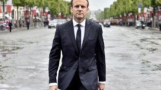 Sous la pluie, Emmanuel Macron participe à sa première cérémonie de ravivage de la Flamme du Souvenir sur la tombe du Soldat inconnu, sous l'Arc de Triomphe. (ALAIN JOCARD / AFP)