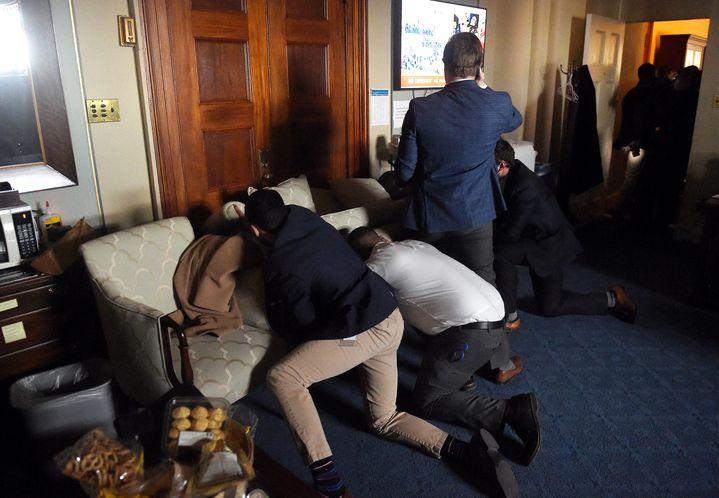 Des employés du Congrès se barricadent dans un bureau alors que des supporters de Donald Trump envahissent le bâtiment, mercredi 6 janvier 2021, à Washington. (OLIVIER DOULIERY / AFP)