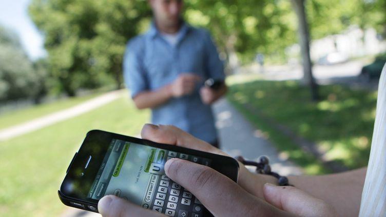 Une personne en train d'envoyer un SMS via son téléphone portable (illustration). (BONNAUD GUILLAUME / MAXPPP)