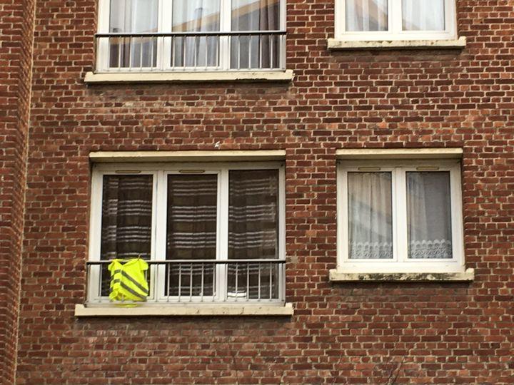 Un gilet jaune suspendu à la fenêtre d'un appartement à Roubaix (Nord), le 10décembre2018. (ELISE LAMBERT/FRANCEINFO)