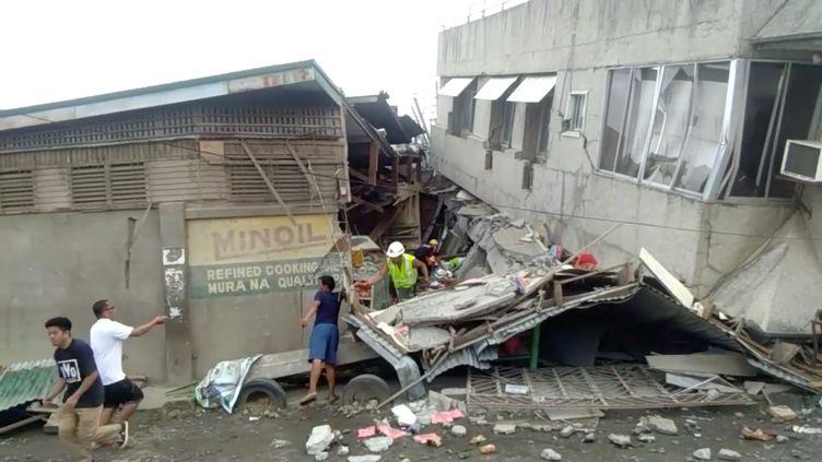 Des secouristes recherchent d'éventuelles victimes dans un bâtiment effondré après le séisme qui a frappé l'île deMindanao (Philippines), dimanche 15 décembre 2019 à Padada. (SOCIAL MEDIA / REUTERS)