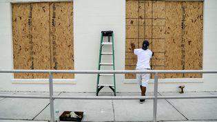 Un homme protège les vitres de son commerce avec des planches à Lake Worth (Floride, Etats-Unis), le 5 septembre 2017. (MAXPPP)
