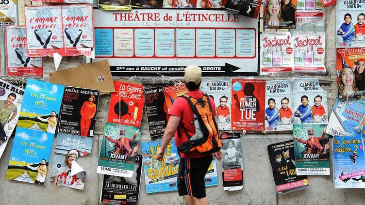 Un passant devant les affiches de la 70ème édition du festival d'Avignon, en 2016. (FERNAND FOURCADE/SIPA)