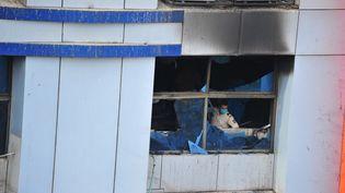 Un policier indien inspecte un hôpital détruit par un incendie à Bombay, le 23 avril 2021. (SACHIN HALDE / ANADOLU AGENCY / AFP)
