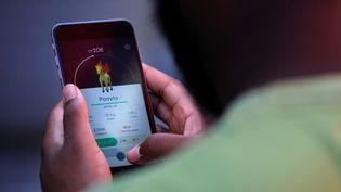 """Un Américain joue à """"Pokémon Go"""" à Times Square, à New York (Etats-Unis), le 11 juillet 2016. (MARK KAUZLARICH / REUTERS)"""