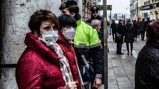 Des visiteurs de Venise (Italie) portent des masques de protection, le 23 février 2020, alors que l'épidémie prend de l'ampleur dans le pays. (MANUEL ROMANO / AFP)