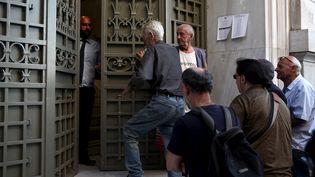 Devant l'entrée d'une banque, le 20 juillet 2015 à Athènes (Grèce). (YIANNIS KOURTOGLOU / REUTERS)
