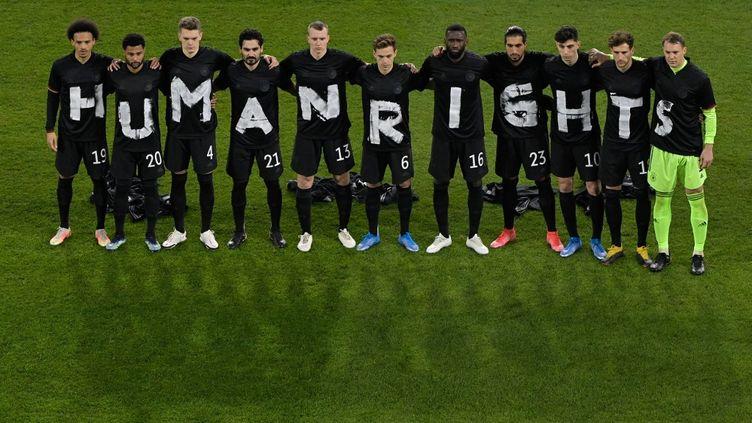 """Les footballeurs allemands portent des tee-shirts formant le mot """"droits humains"""", le 25 mars 2021, lors d'un match de qualification pour la Coupe du monde au Qatar. (TOBIAS SCHWARZ / AFP)"""