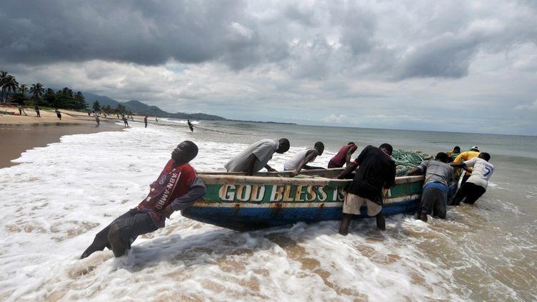 Des pêcheurs mettent à l'eau leur pirogue sur une plage de Freetown en Sierra Leone. (ISSOUF SANOGO / AFP)