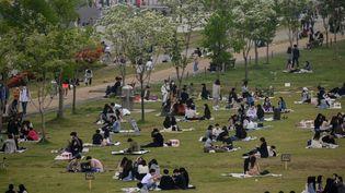 Des personnes profitent de la pelouse d'un parc de Séoul, la capitale sud-coréenne, le 10 mai 2020. (ED JONES / AFP)