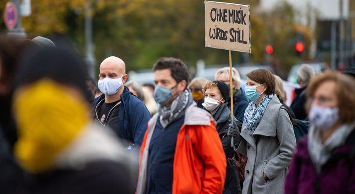 """Munich, 24 octobre 2020. Manifestation d'artistes et autres travailleurs culturels contre les restrictions imposées pour lutter contre la pandémie.  Une femme tend un colis qui dit: """"Sans la musique, ce serait calme"""".  (LINO MIRGELER / DPA)"""
