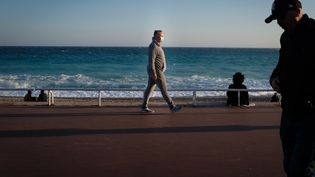 Des passants sur la promenade des Anglais, à Nice (Alpes-Maritimes), le 21 février 2021. (LAURENCE KOURCIA / HANS LUCAS / AFP)