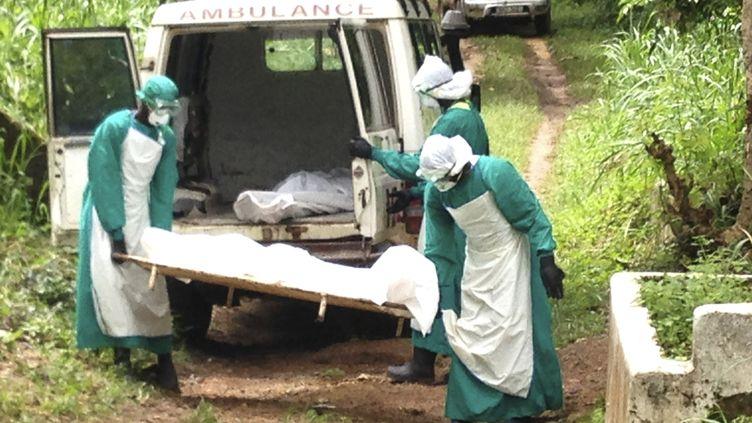 Des employés d'un hôpital transportant des malades morts de l'épidémie de virus Ebola, le 25 juin 2014, à Kenema (Sierra Leone). ( JNA / REUTERS)