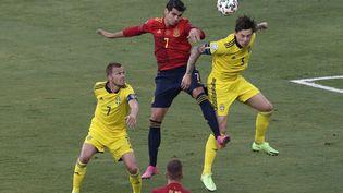 L'Espagnol Alvaro Morata (rouge) au duel avec le SuédoisVictor Lindelof (jaune), lundi 14 juin 2021. (JULIO MUNOZ / AFP)
