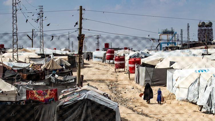 Une femme et un enfant marchent entre des tentes dans le camp d'al-Hol, géré par les Kurdes, où se trouvent des proches présumés de combattants du groupe État islamique (EI), dans le gouvernorat de Hasakeh, au nord-est de la Syrie, le 3 mars 2021. (DELIL SOULEIMAN / AFP)