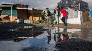 """Des personnes marchent dans la """"jungle"""" de Calais (Pas-de-Calais), le 1er octobre 2016. (JULIEN MATTIA / NURPHOTO / AFP)"""