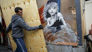 Un ouvrier recouvre une œuvre de Banksy, à Londres, lundi 25 janvier 2016. (TOLGA AKMEN / ANADOLU AGENCY / AFP)