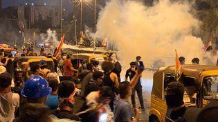 Des policiers font face aux manifestants et font usage de gaz lacrymogènes sur la place Tahrir de Bagdad, en Irak, le 30 octobre 2019. (MURTADHA SUDANI / ANADOLU AGENCY / AFP)