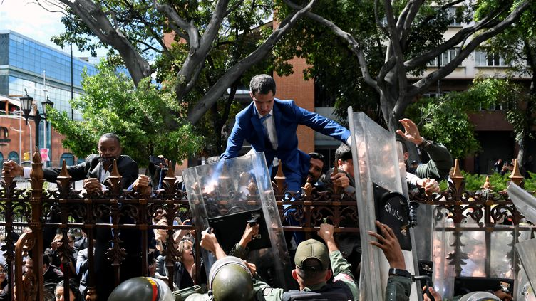 Juan Guaido tente d'escalader les grilles du Parlement vénézuélien le 5 janvier 2020 à Caracas (Venezuela). (FEDERICO PARRA / AFP)