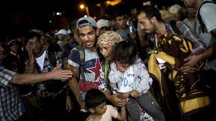 Des migrants attendent un ferry dans le port de l'île de Lesbos, en Grèce, le 7 septembre 2015. (ANGELOS TZORTZINIS / AFP)