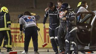 Romain Grosjean épaulé par les secours après son terrible accident lors du GP de Bahreïn (HAMAD I MOHAMMED / POOL)