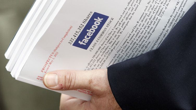 Un investisseur emporte un dossier expliquant l'entrée en Bourse de Facebook, à l'issue d'une réunion organisée par le groupe à Boston (Etats-Unis), le 8 mai 2012. (JESSICA RINALDI / REUTERS)