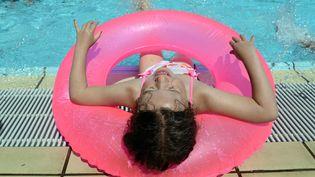 Une petite fille joue dans une piscine publique à Berlin (Allemagne), le 23 juillet 2012. Les météorologues prévoient des températures atteignant 30°C pour les prochains jours. (BRITTA PEDERSEN / AFP)