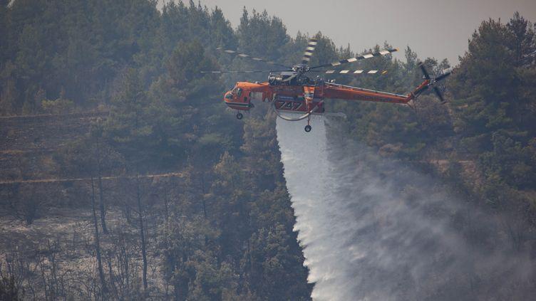 Un hélicoptèreSikorsky S-64 Skycraneengagé dans la lutte contre les incendies à Galatsonas, le 11 août 2021 sur l'île grecque d'Eubée. (NICOLAS ECONOMOU / NURPHOTO / AFP)