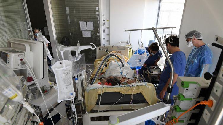 Des soignants au chevet d'un patient, le 8 mars 2021, à l'hôpital Ambroise-Paré, à Boulogne-Billancourt (Hauts-de-Seine). (ALAIN JOCARD / AFP)
