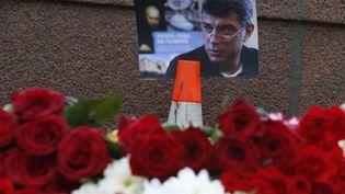 Une photo de Boris Nemtsov et des fleurs déposés sur le lieu où l'opposant russe a été tué de quatre balles, à 100 mètres du Kremlin, le 27 février 2015 à Moscou (Russie). (SERGEI KARPUKHIN / REUTERS)