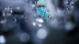Un technicien de laboratoire prépare des réservoirs en acier inoxydable pour accueillir les préparations vaccinales, au centre mondial de distribution de Sanofi à Val-de-Reuil (Eure), le 10 juillet 2020. (JOEL SAGET / AFP)