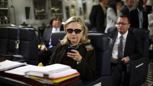 Hillary Clinton, alors secrétaire d'Etat, regarde son téléphone portable dans un avion à destination de Tripoli (Libye), le 18 octobre 2011. (KEVIN LAMARQUE / REUTERS)