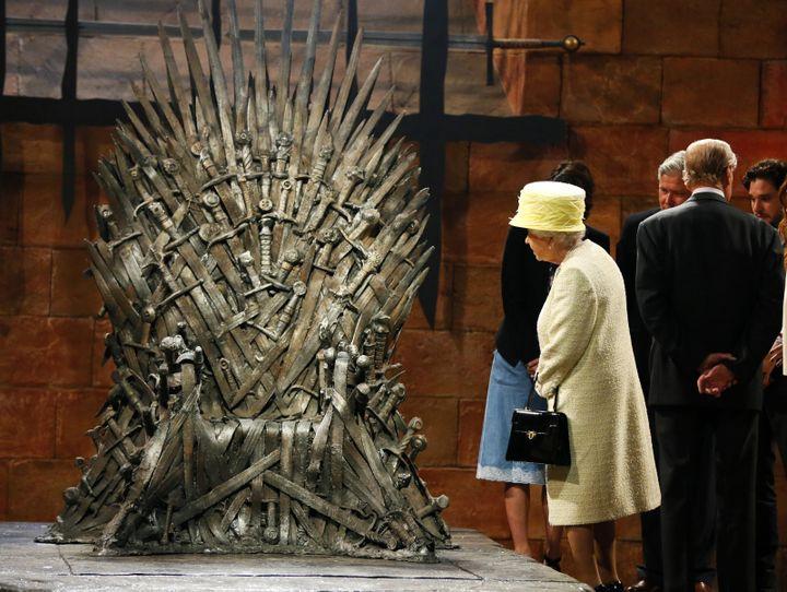 (Un tête couronnée devant un trône. La reine visite l'exposition consacrée à la série Game of Thrones et s'arrête un moment devant l'inconfortable trône de fer. © REUTERS/Phil Noble)