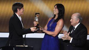 Hope Solo remettant à Abby Wambach le trophée de footballeuse de l'année aux côtés de Sepp Blatter, le 7 janvier 2013 à Zurich (Suisse), lors de la cérémonie du Ballon d'or. (ARND WIEGMANN / REUTERS)