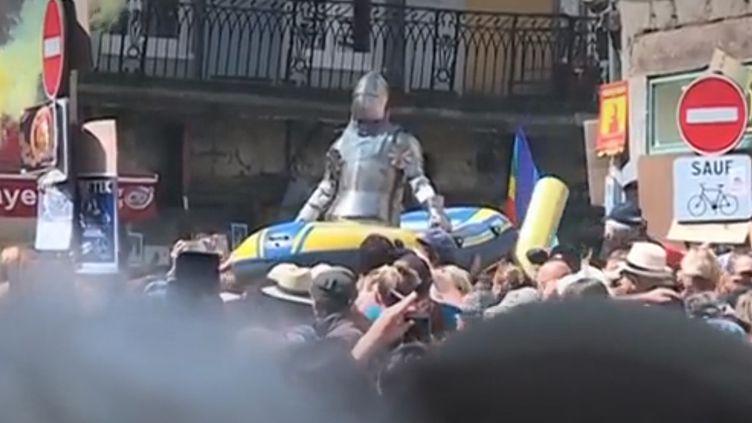 """Un chevalier en armure sur un bateau pneumatique, lui-même porté par des """"gilets jaunes"""", lors du festival internation de théâtre de rue d'Aurillac (Cantal). (france 3)"""