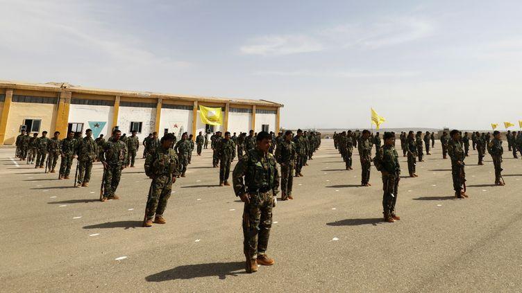 Des membres des Forces démocratiques syriennes participent à une cérémonie près de Deir Ezzor, en Syrie, le 21 mai 2018. (DELIL SOULEIMAN / AFP)