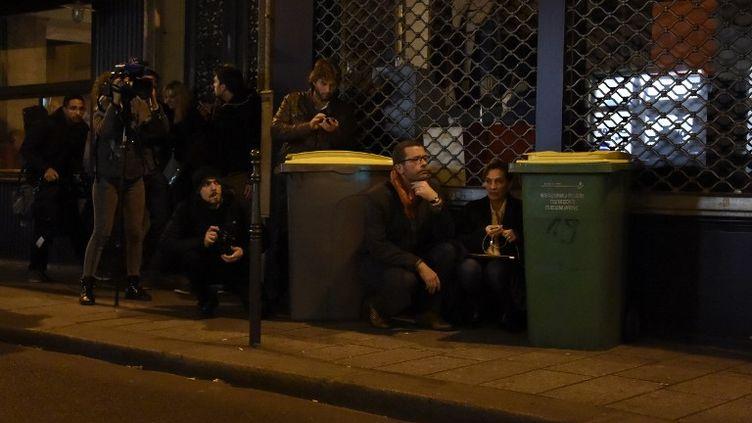 Des personnes, dont des journalistes, se protègent derrière des poubelles à proximité du Bataclan, à Paris. (DOMINIQUE FAGET / AFP)