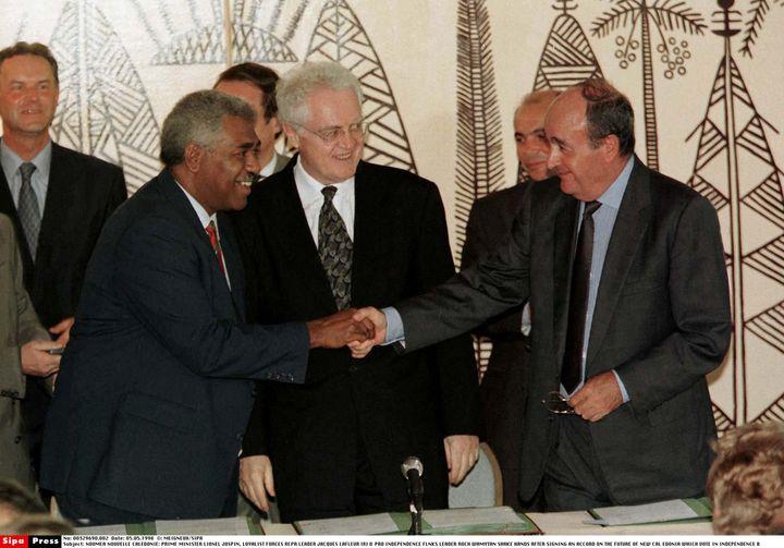 Le Premier ministre, Lionel Jospin (c), observe une poignée de mains entre l'indépendantiste Roch Wamytan (g) et le non-indépendantiste Jacques Lafleur (d), le 5 juin 1998, après la signature d'un accord à Nouméa (Nouvelle-Calédonie). (MEIGNEUX/SIPA)