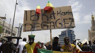 """Des manifestants qui brandissent une pancarte appelant le régime du président malien à """"dégager"""" le 5 juin 2020 dans le cadre d'un rassemblement organisé à Bamako par une coalition dont fait partie le mouvement de l'imam Mahmoud Dicko. (MICHELE CATTANI / AFP)"""