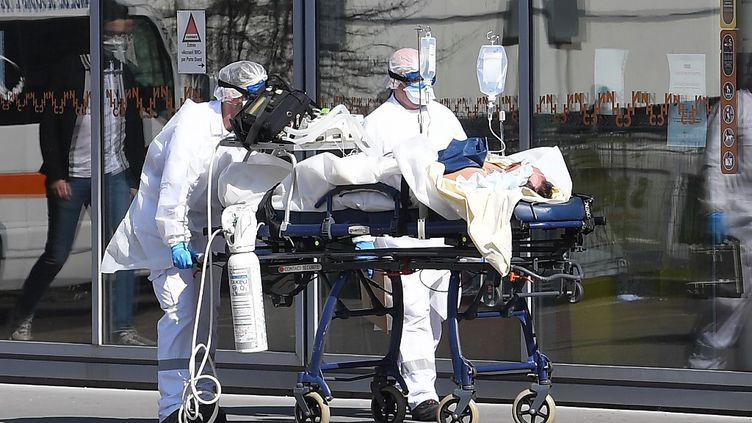 Un patient sous assistance respiratoire est escorté aux hôpitaux universitaires de Strasbourg (Bas-Rhin) par des membres du personnel médical des services d'urgence du SAMU-SMUR, le 16 mars 2020. (PATRICK HERTZOG / AFP)