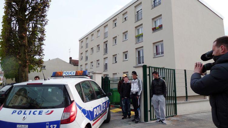 Une voiture de police stationne devant l'immeuble où a été interpellé un suspect qui a été placé en garde à vue dans le cadre de l'enquête sur les quatre meurtres perpétrés avec la même arme en l'espace de cinq mois dans l'Essonne, le 14 avril 2012 à Draveil. (MARJORIE BOYET / AFP)