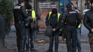 """Des policiers procèdent à des fouilles de sacs de manifestants lors de la mobilisation des """"gilets jaunes"""", à Paris, le 8décembre2018. (NURPHOTO / AFP)"""