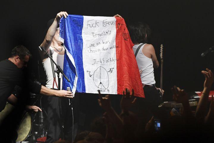 Peter Doherty déploie le drapeau français sur la scène du Bataclan  (BERTRAND GUAY / AFP)