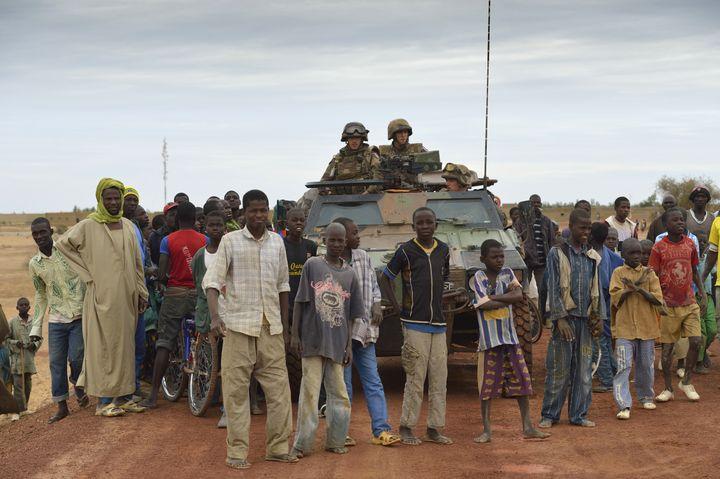 Des Maliens posent avec des soldats français à Tombouctou, le 28 janvier 2013. (ERIC FEFERBERG / AFP)