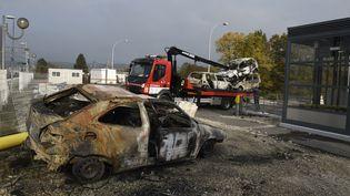 Un camion évacue les voitures brûlées de la voie ferrée, le 21 octobre 2015 à Moirans (Isère). (PHILIPPE DESMAZES / AFP)