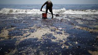 Un homme nettoie la plage de Goleta (Californie, Etats-Unis), le 20 mai 2015, après une fuite de pétrole causée par la rupture d'un oléoduc. (LUCY NICHOLSON / REUTERS)