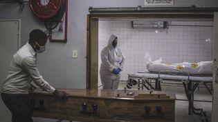 Un employé d'une morgue à côté du corps d'un patient décédé du Covid-19, à Pretoria,le 22 Janvier 2021. (MARCO LONGARI / AFP)