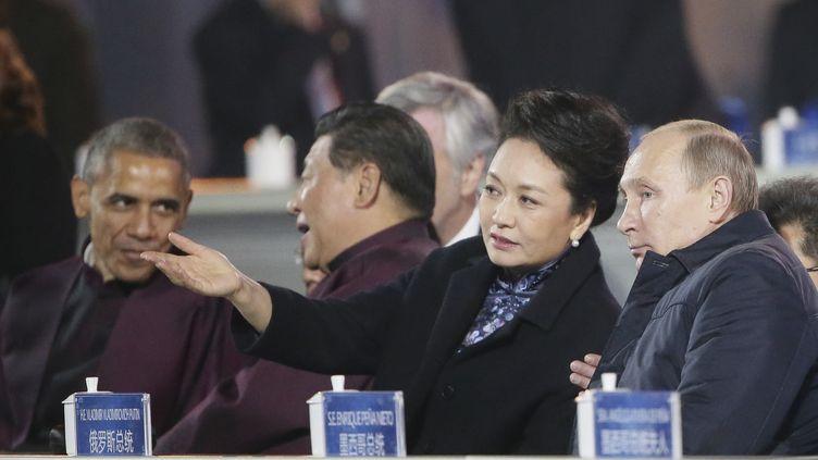 La Première dame chinoise, Peng Liyuan, et le président russe, Vladimir Poutine, en pleine discussion au sommet de l'Apec, le 10 novembre 2014 à Pékin. En arrière-plan, les présidents chinois, Xi Jinping, et américain, Barack Obama. (RIA NOVOSTI / REUTERS)