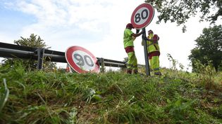 Des employés de la direction interdépartementale des routes de l'Est remplacent des panneaux de limitation de vitesse, près de Wittenheim (Haut-Rhin), le 29 juin 2018. (SEBASTIEN BOZON / AFP)